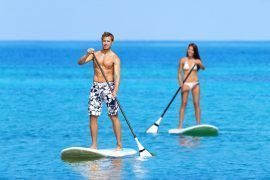 Paddleboard beach people on stand up paddle board surfboard surfing in ocean sea on Big Island, Hawaii Beautiful young multi-ethnic couple, mixed race Asian woman and Caucasian man doing water sport.